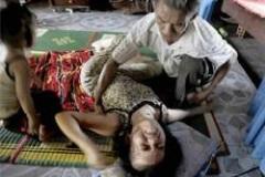 Do Duc Diu, 58, tries to prevent daughter Do Thi Hang, 19, with congenital brain seizures, from injuring herself. Photo: Kuri Takashsashi, Chicago Tribune